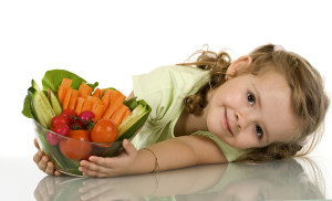 Little girl leaning on the table with a bowl of vegetables - isolated