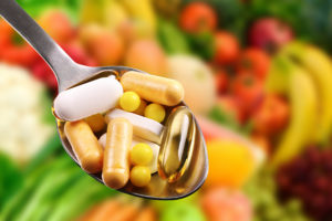 spoon with dietary supplements on fruits background