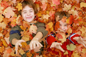 kids-playing-in-autumn-leaves